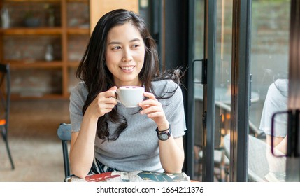 Young beautiful Asian girl holding a cup of coffee in cafe. Girl with coffee. Female traveler, travel vacation fun summer. Young woman drinking coffee at table with notebook in cafe.