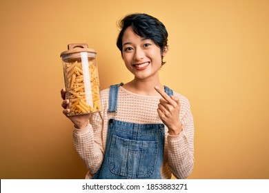 Young beautiful asian girl holding jar with italian dry pasta macaroni over yellow background very happy pointing with hand and finger