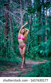 Young beautiful asian girl in pink bikini posing at the tropical forest