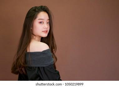 Young beautiful asian girl posting for fashion shoot. Wearing sleeveless black dress.