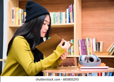 Young beautiful asian girl is reading a book with a bookshelf as background