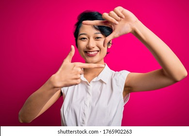 Young beautiful asian girl wearing casual summer shirt standing over isolated pink background smiling making frame with hands and fingers with happy face. Creativity and photography concept.