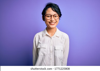 Young beautiful asian girl wearing casual shirt and glasses standing over purple background with a happy and cool smile on face. Lucky person.