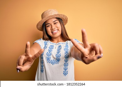 Joven hermosa niña asiática con camiseta informal y sombrero parado sobre fondo amarillo sonriendo con la lengua afuera mostrando dedos de ambas manos haciendo signo de victoria. Número dos.