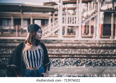 Young beautiful asian hipsters girl wear blackhat pose for take a picture on the railway in the evening vintage style