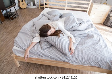 Young beautiful Asian lazy woman sleeping on the bed in vintage cozy bedroom at the morning
