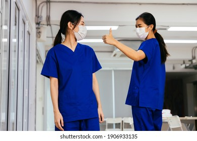Young beautiful Asian medical nurse in scrub uniform wears face mask admire and give thumbs up to coworker at hospital during Covid19 pandemic. Trust and good cooperation in corporate culture concept