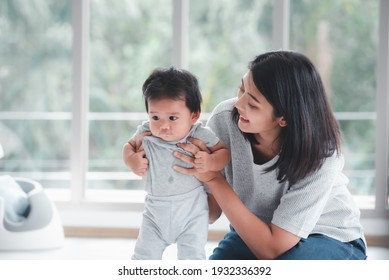 Young beautiful asian mother playing with her baby.