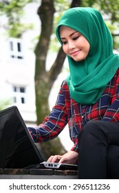 Young beautiful asian muslimah wearing hijab with laptop computer  in green outdoor park university campus  area