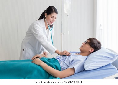 Young beautiful Asian physician using stethoscope checking blood pressure to a patient  who is on the bed in the hospital.