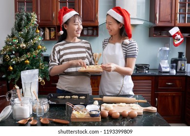 Young beautiful Asian sisters in santa hats laying out cookies on baking sheet and smiling at each other cheerfully in home kitchen