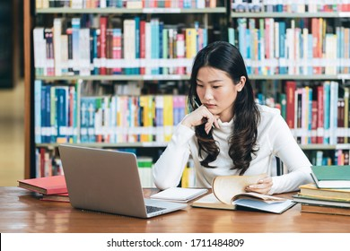 Young beautiful asian student study in the school library and using laptop for online learning.e-Learning education concept.Back to school