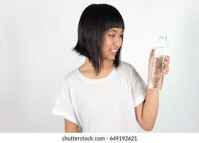 Young beautiful asian teenage girl holding bottle of water isolated against white background