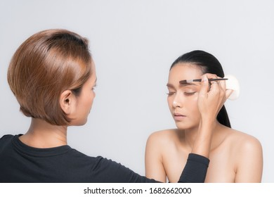 Young beautiful asian woman applying makeup by makeup artist on location.