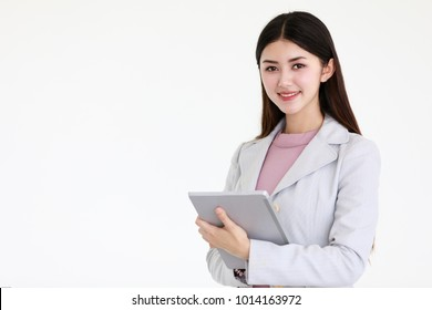 Young beautiful Asian woman with black long hair standing in front of white background, tablet computer in hands