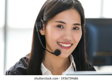 Young and beautiful Asian woman call center officer wearing microphone headset and happy working with a friendly face and positive service mind.