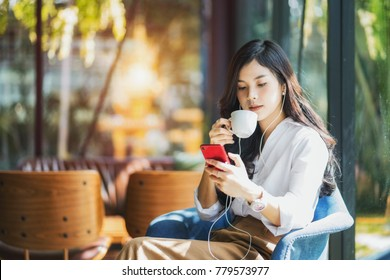 Young beautiful asian woman close her eyes and listening to music from smartphone while relax in cafe with happiness