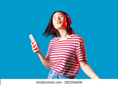 Young beautiful asian woman dancing indoor on blue baground holding smartphone - Isolated diverse female clubbing listening streaming music - happiness, excitement, dancing concept