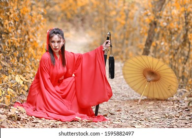 Young beautiful asian woman dress in traditional Chinese old fashion warrior style with ancient word and umbrella. Cute girl in red dress sitting and looking at camera outdoor. Travel in Asia concept