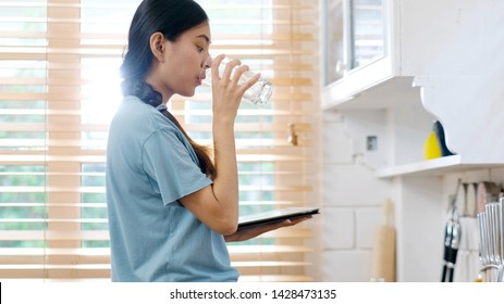 Young beautiful asian woman drinking water while holding digital tablet and standing by window in kitchen background, peolpe and healthy lifestyles