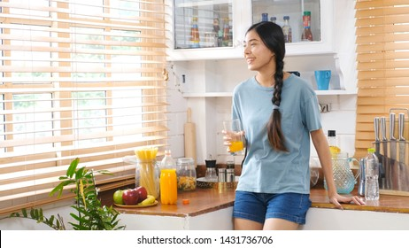 Young beautiful asian woman drinking orange juice and smiling while standing by window in kitchen background, peolpe and healthy lifestyles
