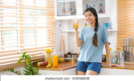 Young beautiful asian woman drinking orange juice and smiling while standing by window in kitchen background, Happy asian teenager woman holding glass of orange juice, Food and drink healthy lifestyle