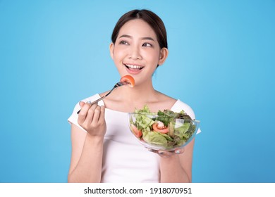 Young beautiful Asian woman eating a salad, Isolated on blue background.