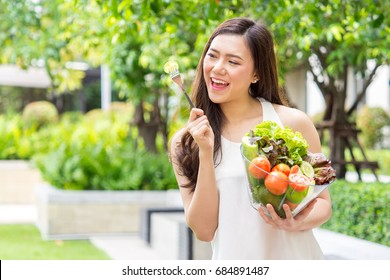 Young beautiful asian woman eating fresh clean food with cucumber vegetables and fruits for good healthy over green background, healthy food woman for diet