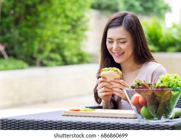 Young beautiful asian woman eating fresh clean food sandwich with vegetables and fruits for good healthy over green background, healthy food woman for diet