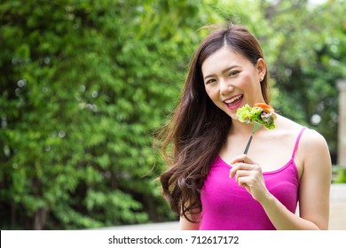 Young beautiful asian woman eating fresh clean food with tomato vegetables and fruits for good healthy over green background, healthy food woman for diet