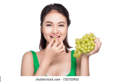 Young beautiful asian woman eating fresh grapes isolated on white background