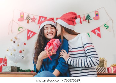 Young beautiful Asian woman give gift box and kiss to best women friend.Smiling face in room with Christmas tree decoration for holiday background.Christmas Party and celebration concept.