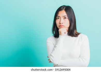 Young beautiful Asian woman hand near the face and thinking, Portrait  female touch chin dream dreamy having doubts, studio shot isolated on a blue background