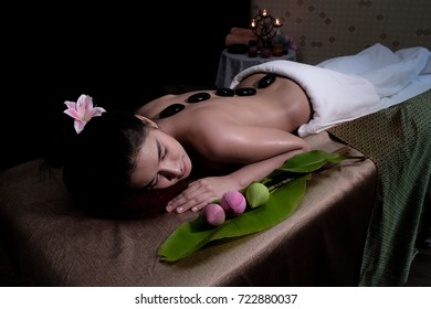 Young beautiful Asian woman having hot stone massage in spa, Thailand