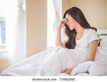 Young beautiful asian woman headache on white bed, sad, migraine stressed, crying, disappointed feeling in the morning