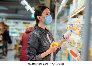 A young beautiful Asian woman is inside a supermarket, shopping for groceries, while wearing a medical mask. Communicate about health and safety measures in commonly used spaces, it times of pandemic