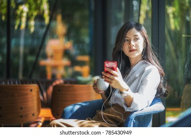 Young beautiful asian woman listening to music from smartphone while relax in cafe with happiness