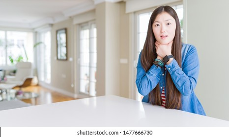 Young beautiful asian woman with long hair wearing denim jacket shouting suffocate because painful strangle. Health problem. Asphyxiate and suicide concept.