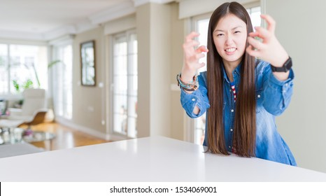 Young beautiful asian woman with long hair wearing denim jacket Shouting frustrated with rage, hands trying to strangle, yelling mad