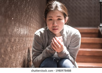 young beautiful Asian woman in pain suffering depression - dramatic indoors portrait on staircase of sad and depressed Japanese girl as victim of bullying and abuse