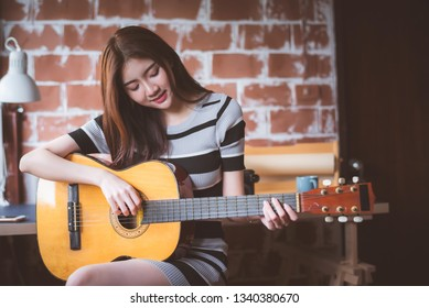 Young beautiful Asian woman is playing acoustic guitar at her working room, vintage warm tone.