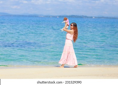 a young beautiful asian woman playing with the puppy on the beach, Munnork island, Rayong, Thailand