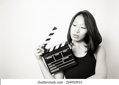 Young beautiful asian woman portrait, black dress, looking at  clapperboard, in black and white