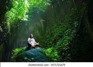 young beautiful Asian woman practicing Yoga posing sitting in lotus position meditating over a stone in a stunning natural landscape full of vegetation and green in healthy lifestyle and relaxation