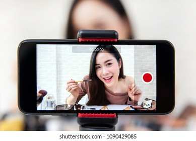 Young beautiful Asian woman professional beauty vlogger or blogger recording make up tutorial video by smartphone to share on social media