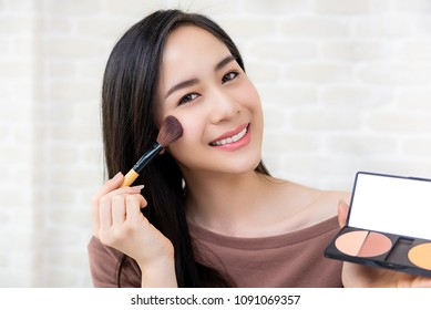 Young beautiful Asian woman professional beauty vlogger or blogger  doing a make up tutorial
