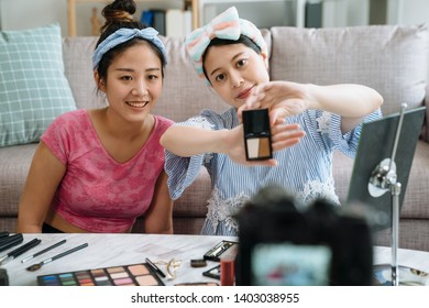 Young beautiful Asian woman professional beauty vlogger with friend blogger recording makeup tutorial video to share on social media. lady holding cosmetic products showing to professional camera.