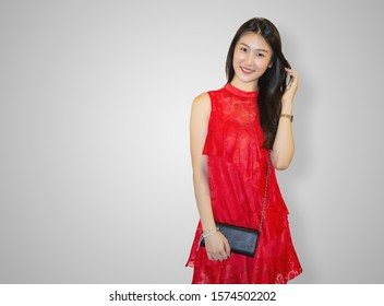 Young and beautiful Asian woman in a red dress posing over white background.