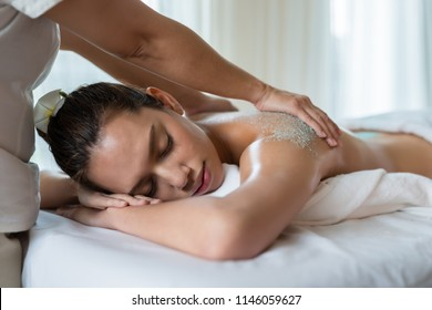 Young beautiful Asian woman relaxing in the spa massage and having salt scrub massage at back. healthy lifestyle and relaxation concept.