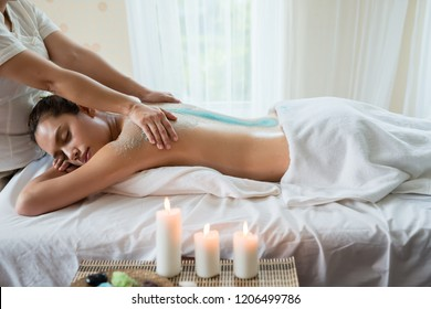 Young beautiful Asian woman relaxing in the spa massage and having salt scrub massage at back. healthy lifestyle and relaxation concept. Select focus hand of masseuse